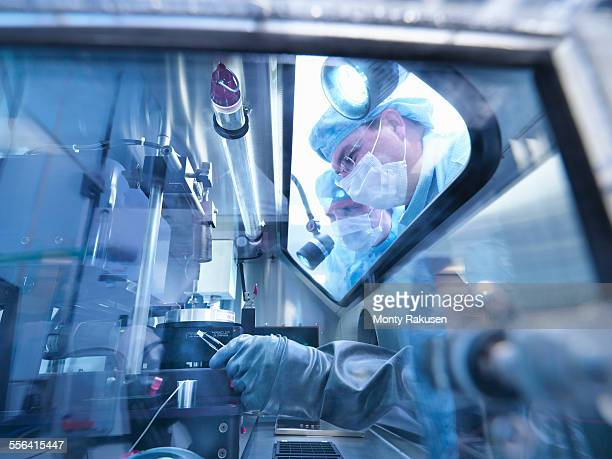 electronics workers looking into sealed work station window in clean room laboratory - 半導体 ストックフォトと画像