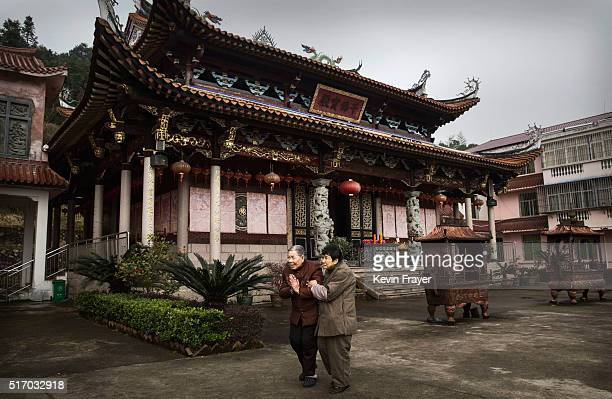SHA COUNTY CHINA MARCH 17 Eledery Chinese residents walk in front of the Ji Xiang Temple and nursing home during a pause in the rains on March 17...