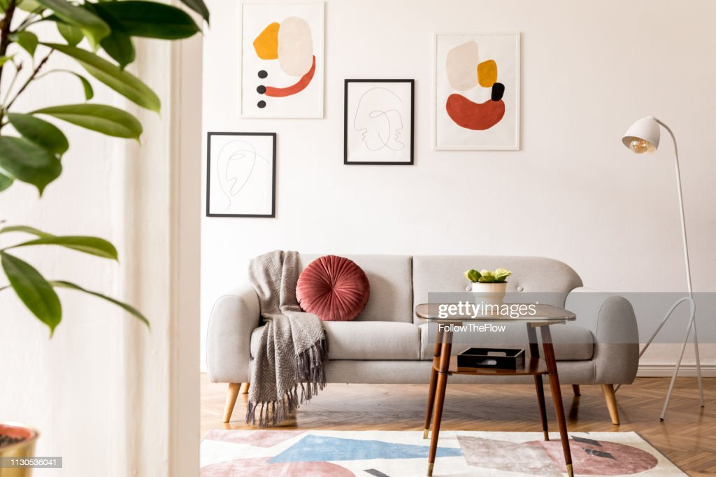 Elegant and vintage apartment interior with classic wooden furniture, grey sofa, retro coffee table, lamp and mock up posters gallery. Brwon parquet, stylish carpet and plants. Bright space. : Stock Photo