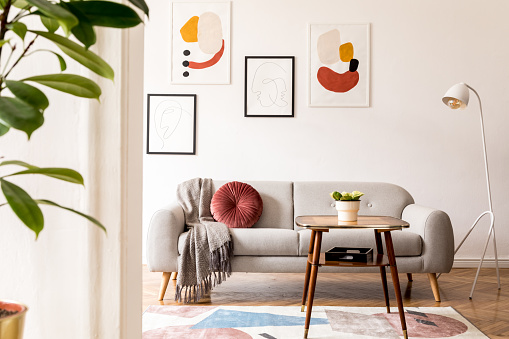 Elegant and vintage apartment interior with classic wooden furniture, grey sofa, retro coffee table, lamp and mock up posters gallery. Brwon parquet, stylish carpet and plants. Bright space. 1130536041