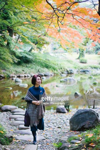 elegant asian woman standing in public garden - robe longue photos et images de collection