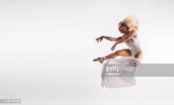スタジオでジャンプ白いドレスでエレガントなバレエダンサー - チュール生地 ストックフォトと画像