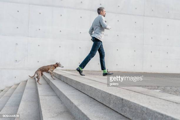 elegant bearded businessman racing up stairs with dog outdoors