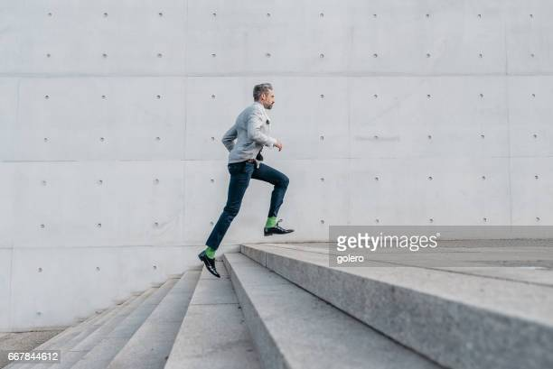 elegant bearded businessman running up stairs outdoors - stairs stock photos and pictures