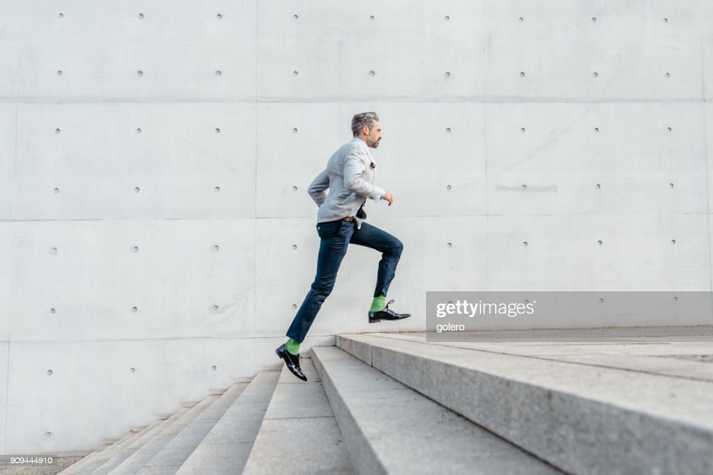 elegant bearded businessman running up stairs outdoors : Stock Photo
