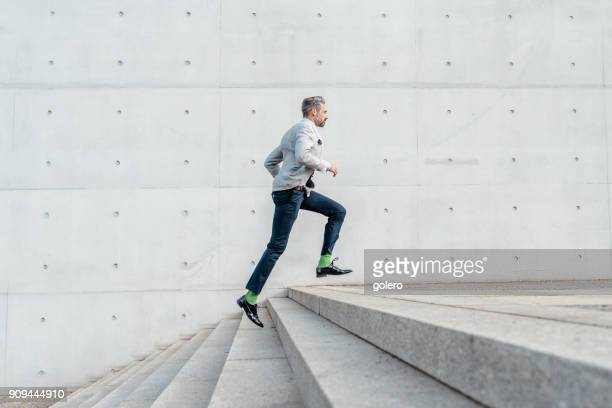 elegant bearded businessman running up stairs outdoors
