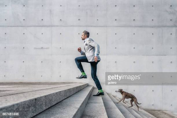 elegant bearded businessman running up stairs with dog in city