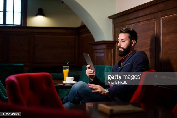 elegant bearded man drinking coffee and using tablet - sports betting stock pictures, royalty-free photos & images