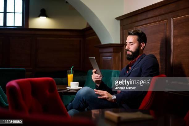 エレガントなひげを生やしている男コーヒーを飲んでタブレットを使う - スポーツ・ベッティング ストックフォトと画像