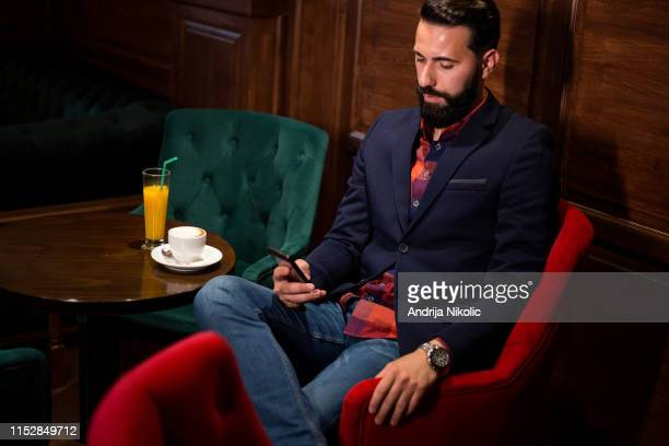 elegant bearded man drinking coffee and using tablet - charging sports stock pictures, royalty-free photos & images