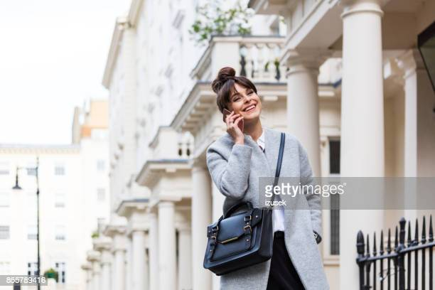elegant beautiful woman talking on phone in front of city houses - gray coat stock pictures, royalty-free photos & images