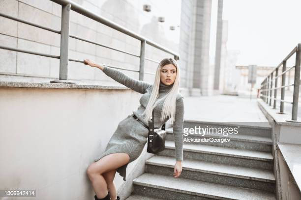 elegant blond female holding on metal railing near stairs outside - bending over in skirt stock pictures, royalty-free photos & images