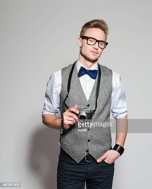 エレガントなブロンドを着ている若いビジネスマンのツイードベストとリボン紐