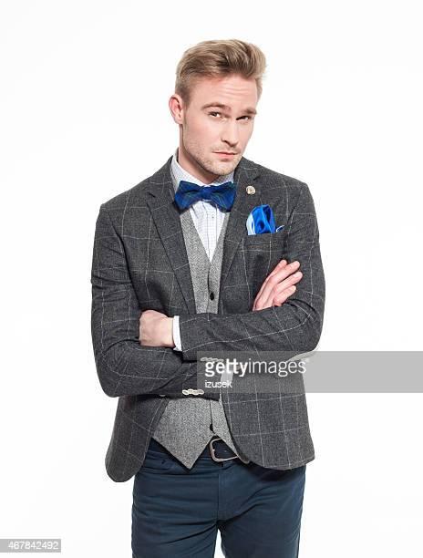 エレガントなブロンドを着ている若い男性のツイードジャケットとリボン紐