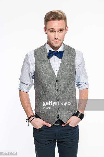 elegant blonde young man wearing tweed vest and bow tie - waistcoat stock photos and pictures