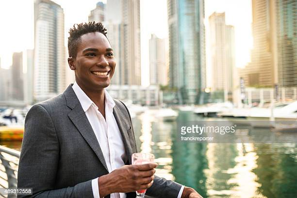 Elegant businessman drinking an orange juice in Dubai Marina