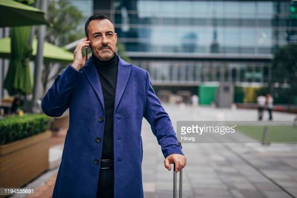 elegant businessman is talking on phone - purple coat stock pictures, royalty-free photos & images