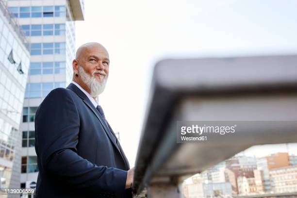 elegant businessman leaning on railing  in the city, looking sceptical - orecchini foto e immagini stock