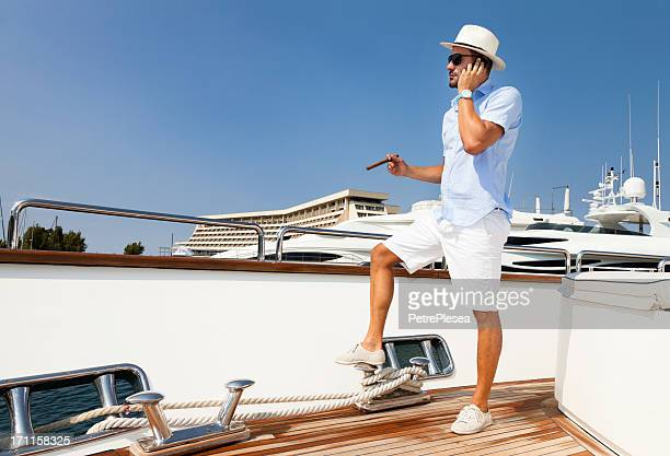Elegant Businessman on board of the yacht. Phone conversation.