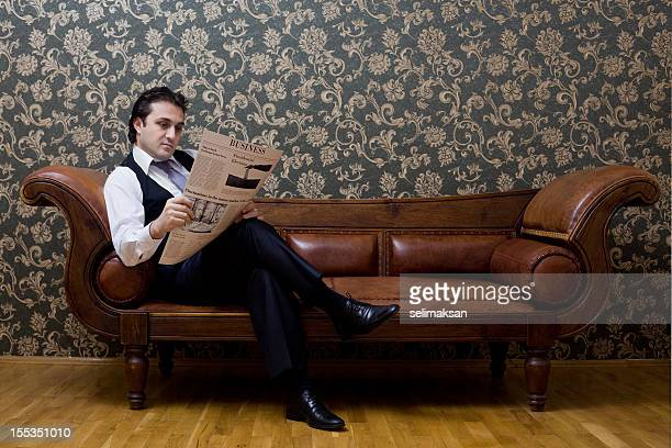 Elegant businessman sitting on sofa and reading newspaper