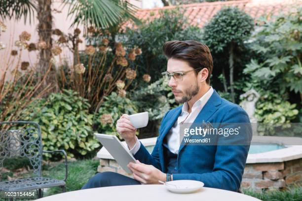 elegant businessman using tablet in a garden cafe - italian man stock photos and pictures