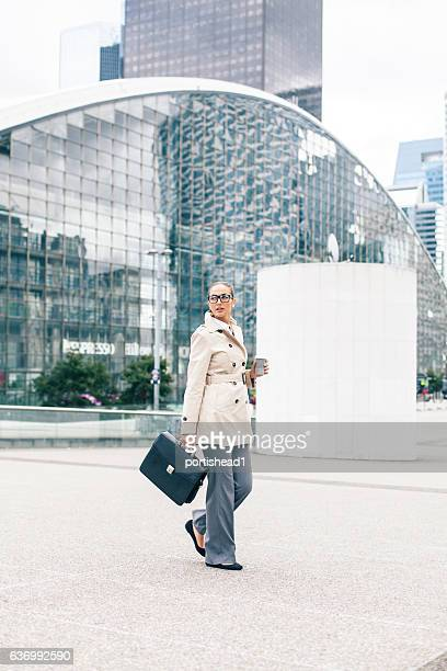Elegant businesswoman holding business bag and walking on street