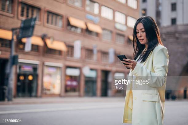 elegant businesswoman text messaging - yellow blazer stock photos and pictures