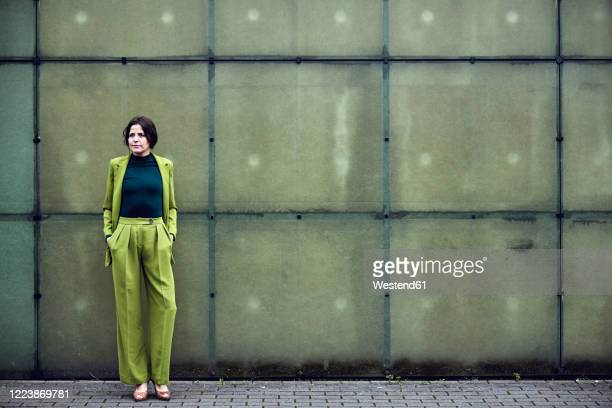 elegant businesswoman wearing green suit standing at a wall - pant suit stock pictures, royalty-free photos & images