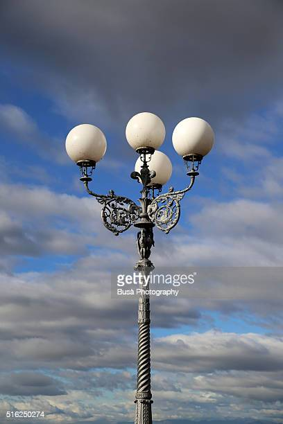 Elegant cast-iron street lamp against a moody sky in Florence, Italy