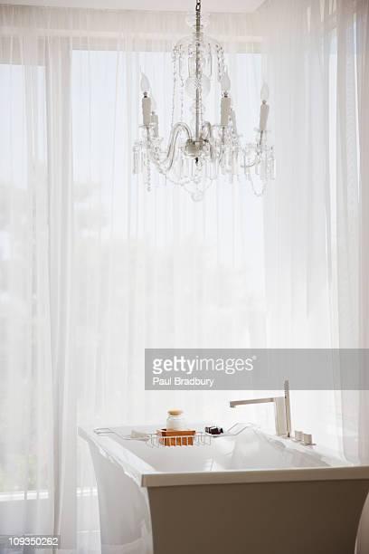 Elegant chandelier and modern bathtub in bathroom