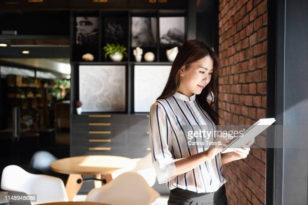 elegant chinese business woman using a tablet in an office - using digital tablet stock pictures, royalty-free photos & images