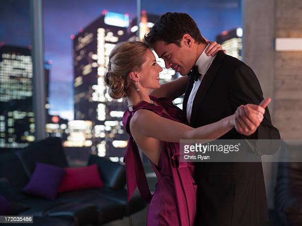 elegant couple dancing in living room - evening gown stock photos and pictures