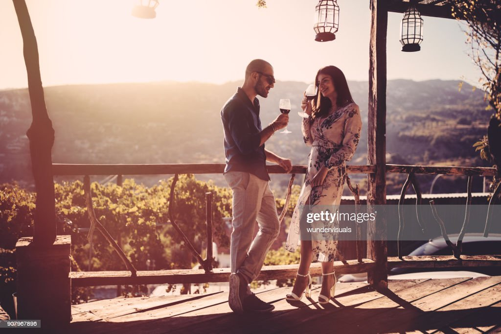 Elegant couple drinking red wine at French rustic vineyard winery : Stock Photo