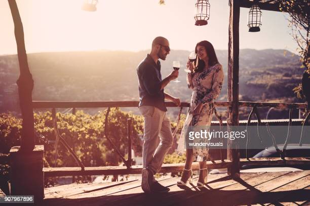 elegant couple drinking red wine at french rustic vineyard winery - vintage restaurant stock pictures, royalty-free photos & images