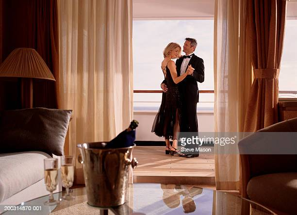Elegant couple embracing in cruise ship cabin