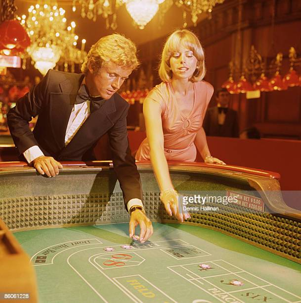 elegant couple gambling at craps table - gambling table stock pictures, royalty-free photos & images