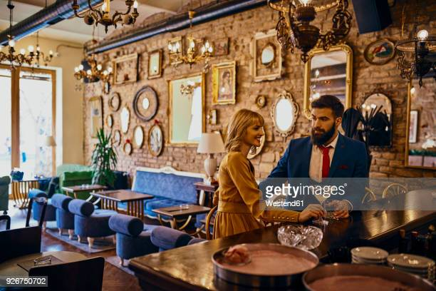 elegant couple having a drink in a bar - bourbon whisky foto e immagini stock