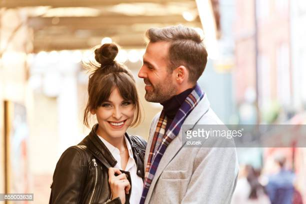 Elegant couple in the city, beautiful woman smiling at camera
