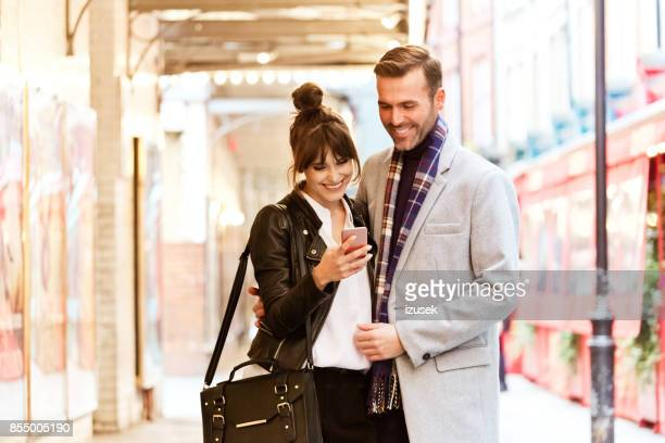 elegant couple in the city, beautiful woman using smart phone - izusek stock photos and pictures