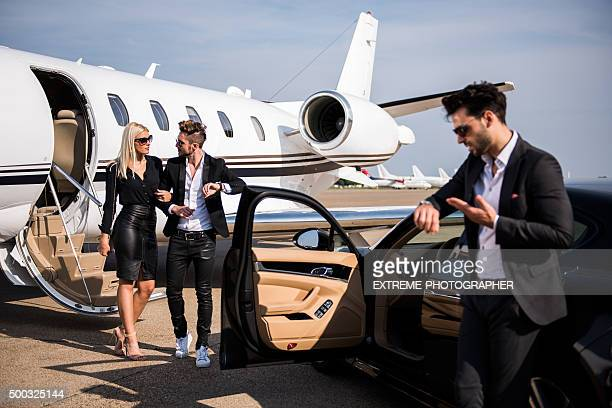 Elegant couple leaving private airplane