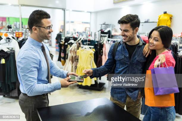 Elegant couple paying with credit card in shopping mall