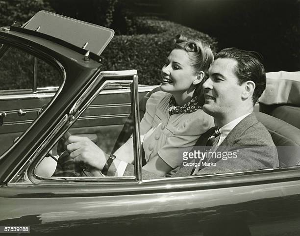Elegant couple riding in in convertible car, (B&W)