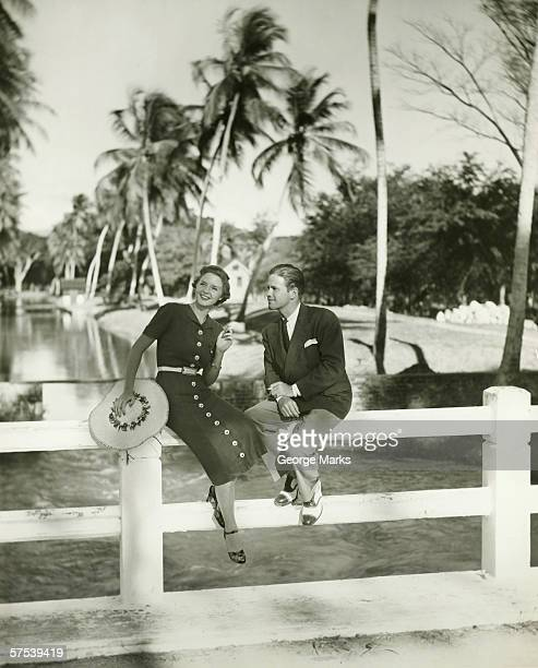 Elegant couple sitting on fence in tropical environment, (B&W)