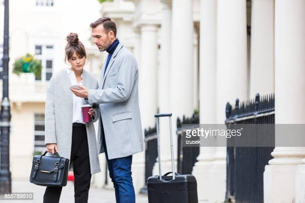 elegant couple standing in the city street, man holding mobile phone - a fall from grace stock pictures, royalty-free photos & images