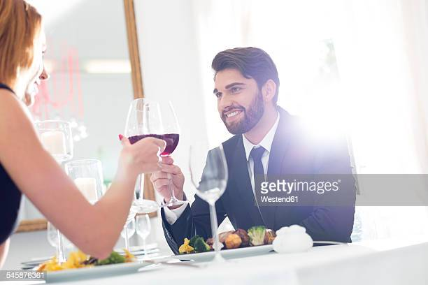 Elegant couple toasting wine glasses in restaurant