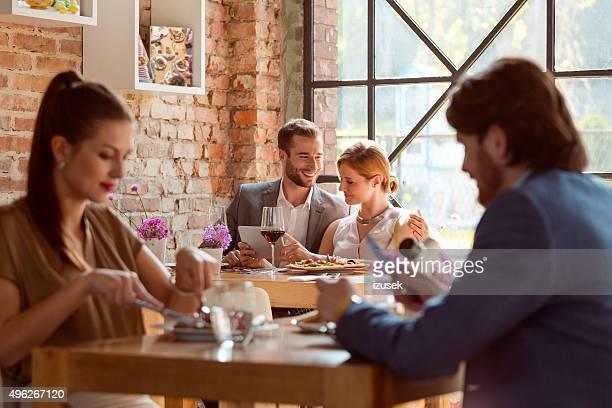 Élégant couple à l'aide d'une tablette numérique dans le restaurant