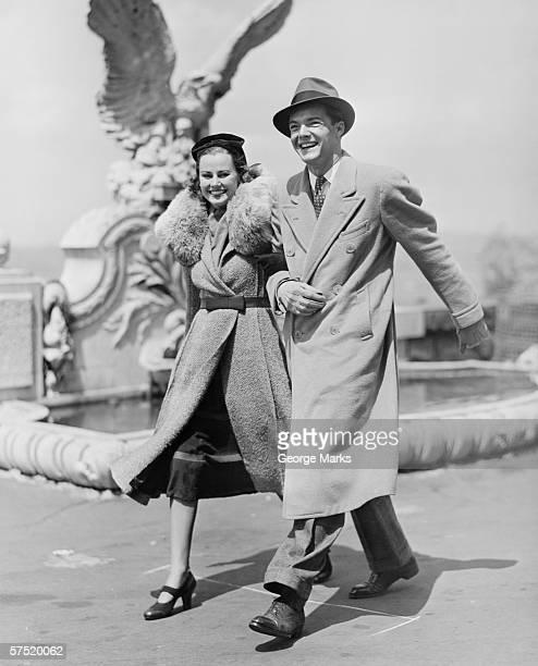 Elegant couple walking on promenade, (B&W)