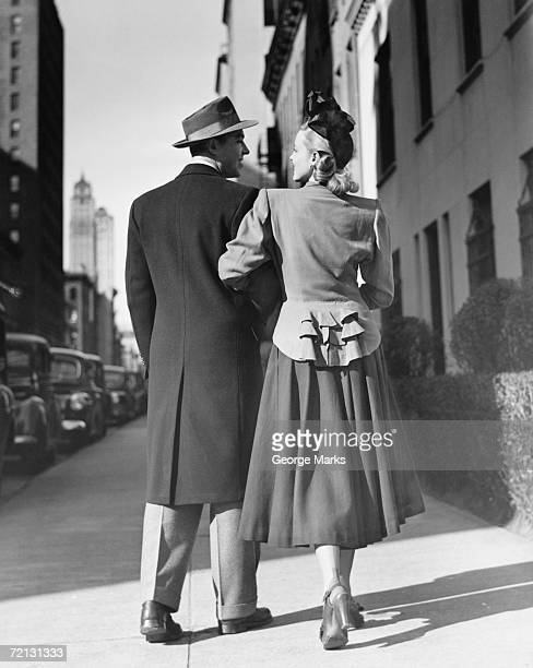 elegant couple walking on street, (rear view) (b&w) - fedora stock pictures, royalty-free photos & images