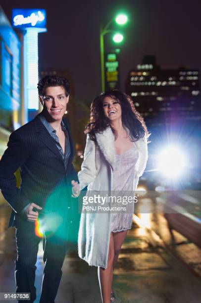 Elegant couple walking on urban street at night