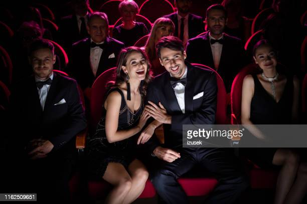 elegant couple watching comedy movie in the cinema - opera stock pictures, royalty-free photos & images